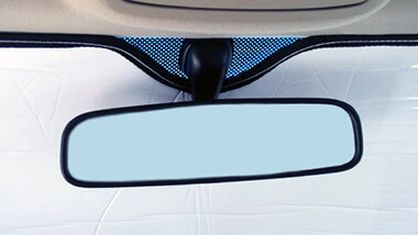 Heatshield windshield shades are secured using the rear view mirror for support